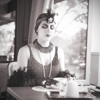 Retro Woman 1920s - 1930s Sitting with Cup of Tea