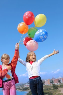 Two Girl Holding Colorful Helium Balloons in the Sky