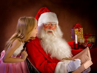 Little Girl Talking to Santa Clause While He Writes Magic Feathe