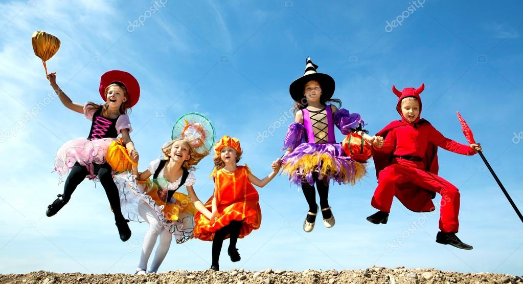 Five Happy Children Running Together to Trick or Treat in the Halloween Costumes of Witches and Devil at the Blue Sky.