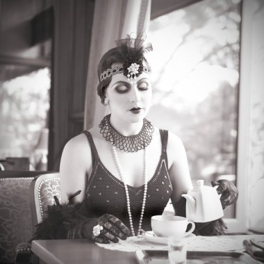 Retro Woman 1920s - 1930s Sitting with in a Restaurant Holding a