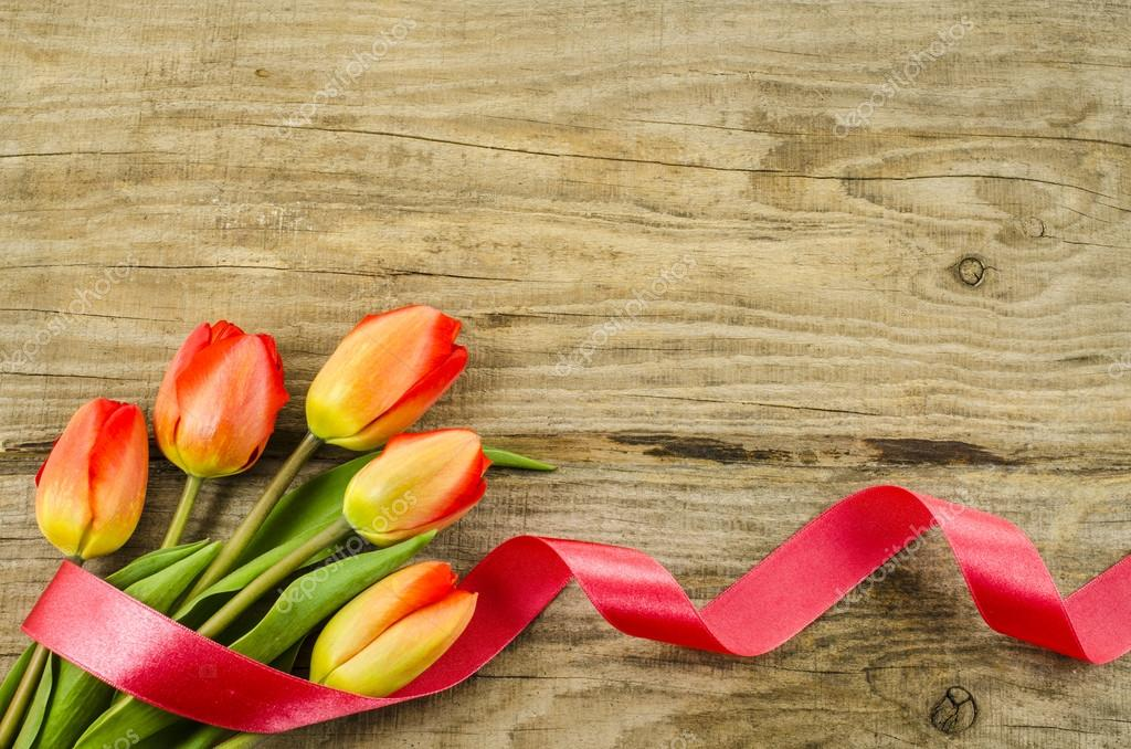 Empty wooden background with colorful flowers and red ribbon