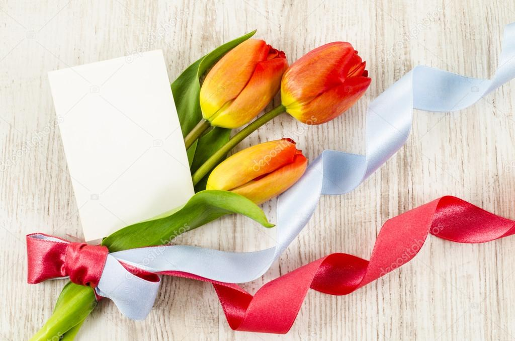 Empty postcard with flowers and ribbon on wooden background