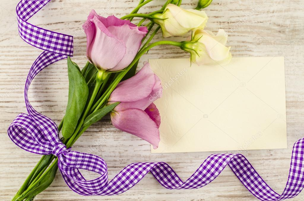 Empty postcard, flower and purple ribbon on wooden background