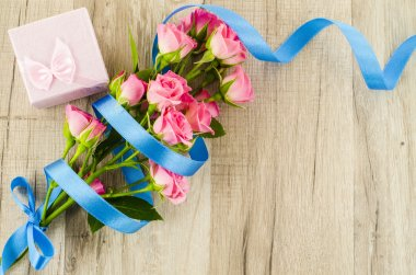 Empty wooden background with colorful flowers and blue ribbon