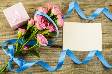 Empty postcard, flower and blue ribbon on wooden background