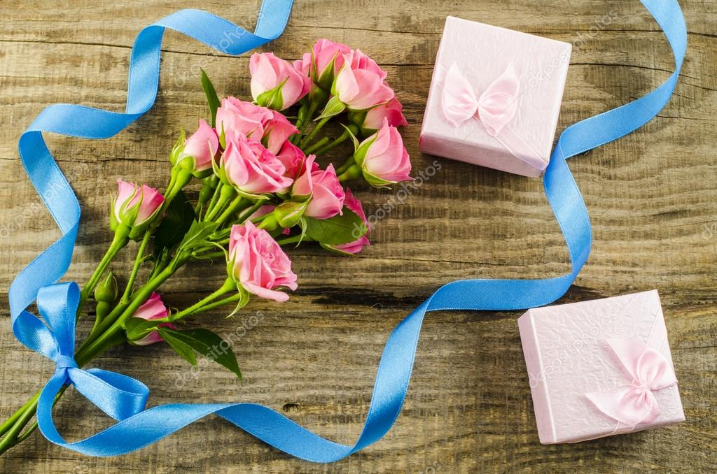 Rose flower and gift box on wooden background
