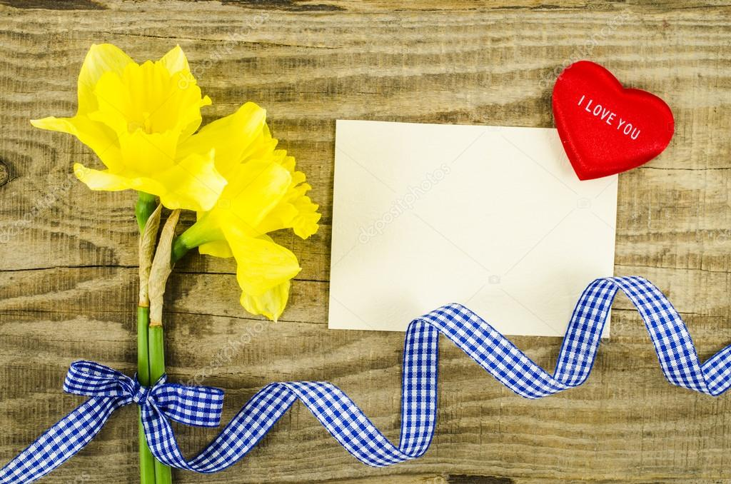 Empty card with flower and ribbon on wooden background