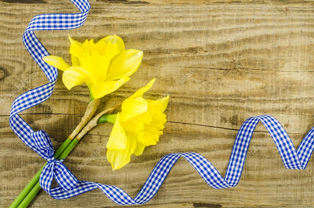 Flower with blue ribbon on wooden table