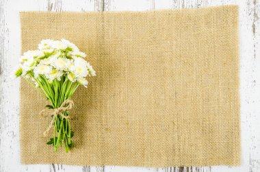 Fresh flowers on jute background
