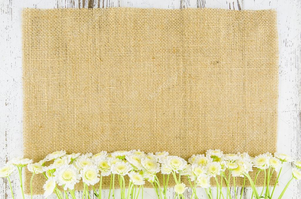 Fresh flowers on jute background