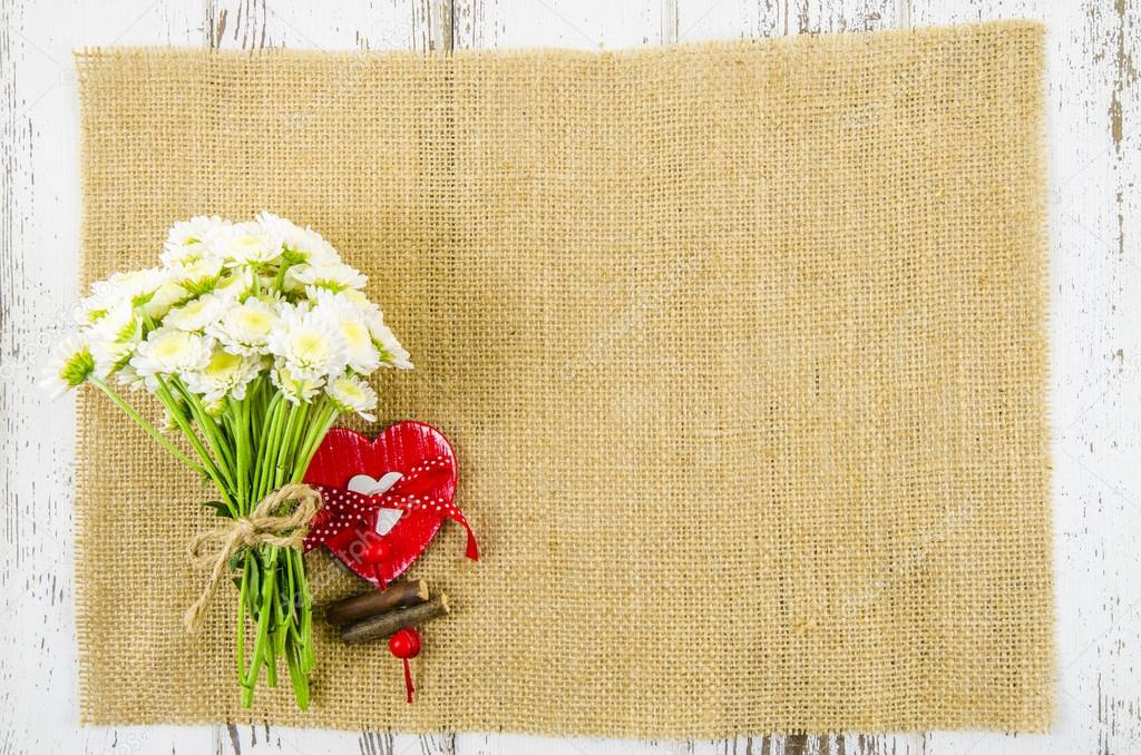 Flowers with heart on jute background