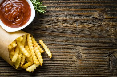 French fries over old wooden table