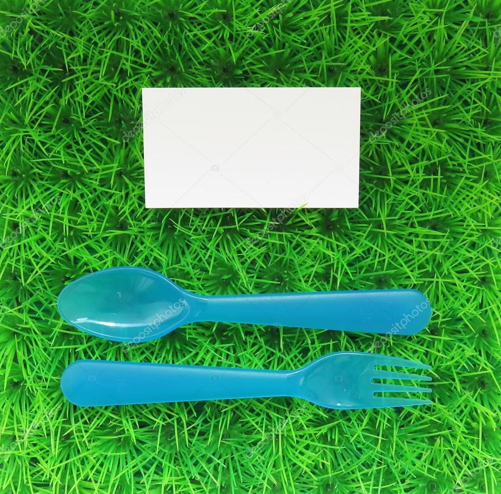 Plastic fork and spoon on a green lawn with a business card top