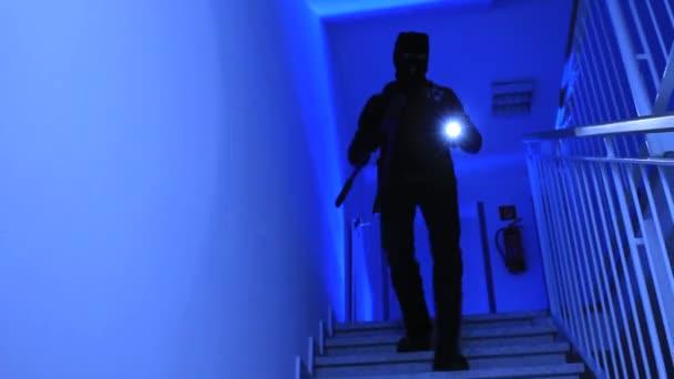 Ein Einbrecher kommt die Treppe hinunter.