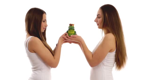 Young girls kissing toy frog