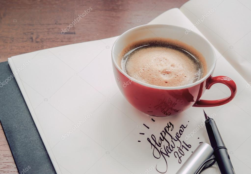 A cup of coffee resting on a book with text happy new year 2016.