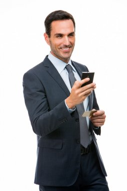 Half length portrait of a smiling businessman holding mobile phone and credit card