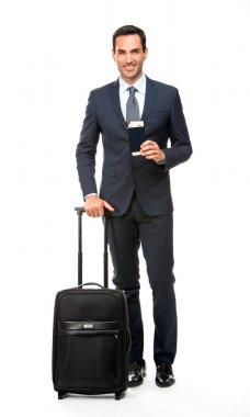 Full length portrait of a smiling businessman with trolley and holding his passport