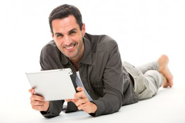 Man laying on the floor, smiling at camera and holding his digital tablet with both hands