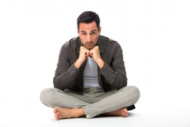 Thoughtful man sitted on the floor with the hands under his chin