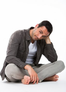 Thoughtful man sitted on the floor, looking at camera and holding his head with one hand