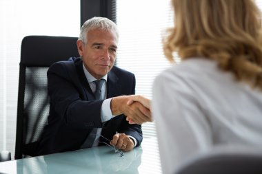 Two businesspeople, male and female, shaking hands during a meeting in the office