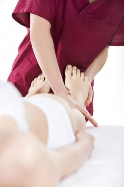 Physical therapist who does the foot reflexology to a woman