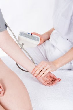 Doctor gets measure the blood  pressure to woman patient
