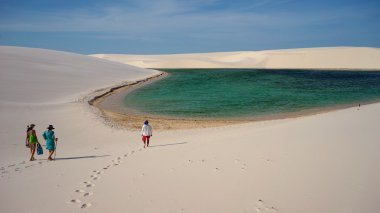 Tourists, lagoon and dunes at Grandes Lencois, Lencois Maranhenses, Maranhao, Brazil
