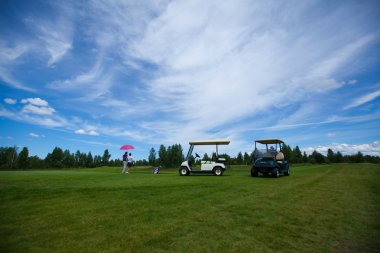 two golf carts on the golfe course in summer