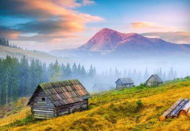 Sunrise above the high montain foggy valley with old wooden houses on a hill in a mountain forest. The Goverla, higher mountain of Ukraine, on a skyline. stock vector