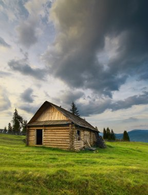 Mountain landscape with wooden house