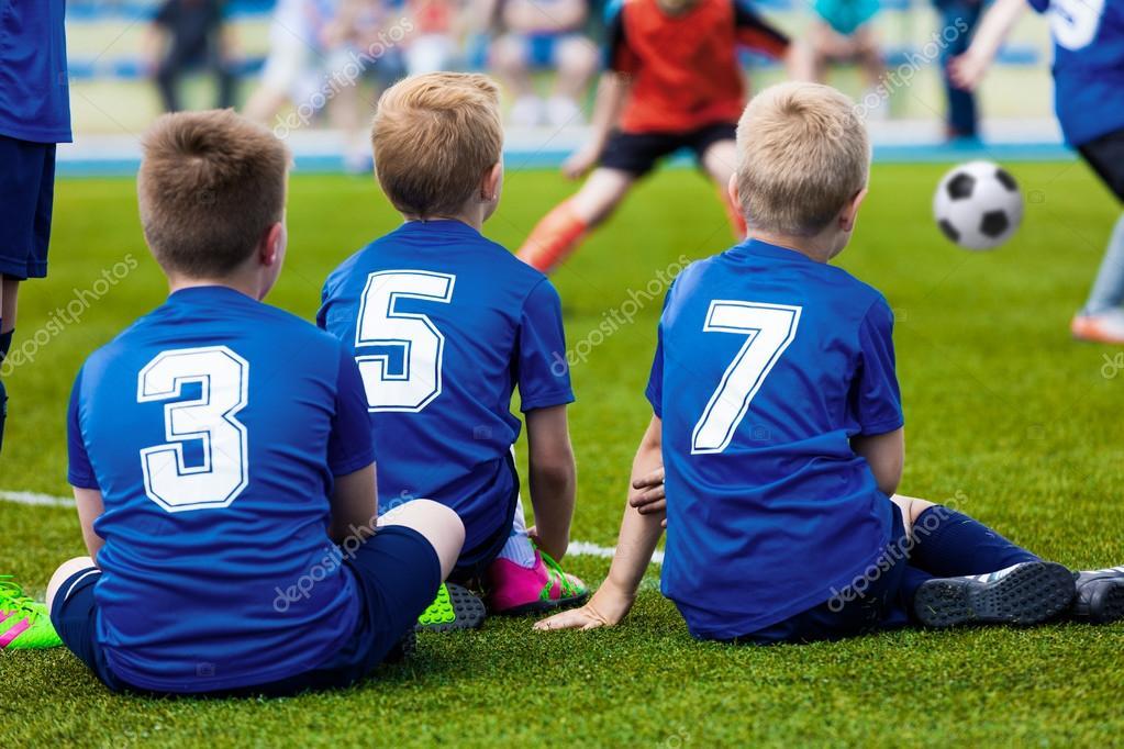 2439c2ce483c6 Chicos en uniformes de deporte azul como reserva de jugadores sentados en  el campo de fútbol y viendo fútbol partido - niños con uniforme azul — Foto  ...