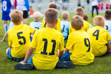 Children soccer football team at the sport stadium. Boys sitting on football pitch during school soccer tournament