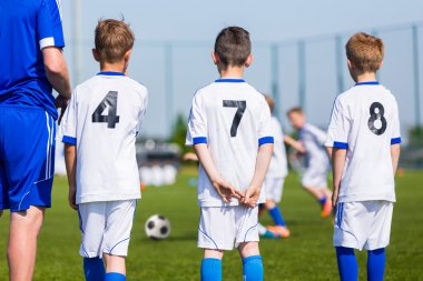Football soccer match for children. Boys and coach waiting on a