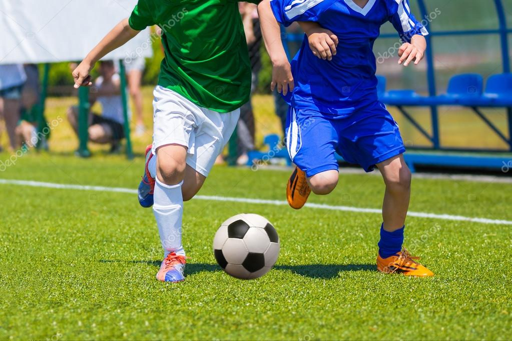 b0ff8cdb44a77 Chicos jóvenes jugando fútbol. Dura competencia entre los jugadores correr  y patear la pelota de fútbol. Juego final del torneo de fútbol para niños.