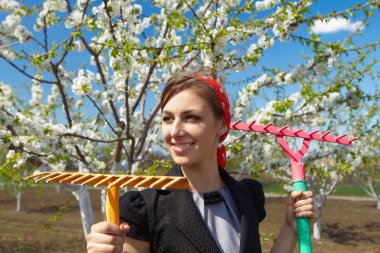female with rakes on garden