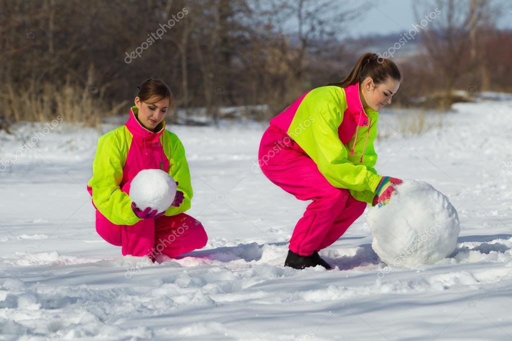 girls rolling huge snowball