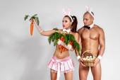 Fotografie Couple in rabbit costumes with carrots and eggs