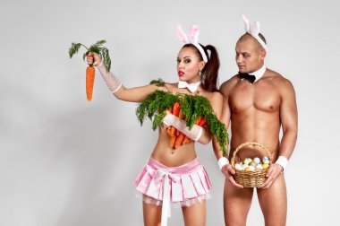 Couple in rabbit costumes with carrots and eggs