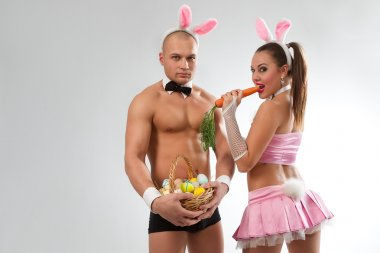 Couple in rabbit costumes with carrot and eggs