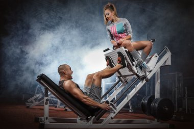 Man doing legs presses with  trainer