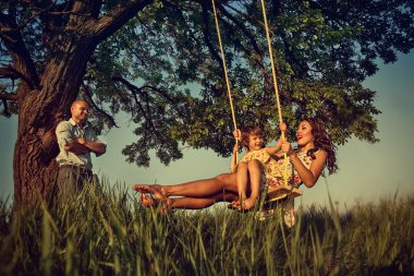Girl and mother on the swing