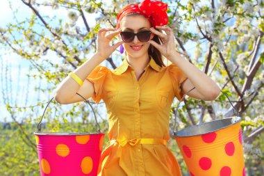 Girl with buckets in garden