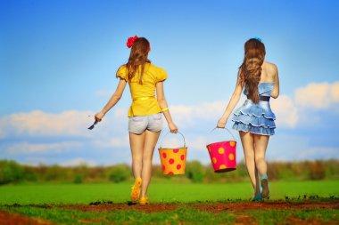 Girls walking with  buckets