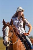 Fotografie Mädchen Ridinga Pferd gegen blauen Himmel