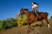 Mädchen reitet Pferd auf dem Land.