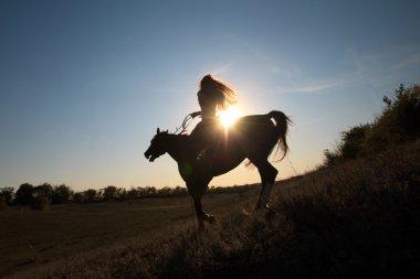 Girl riding  horse  against sun