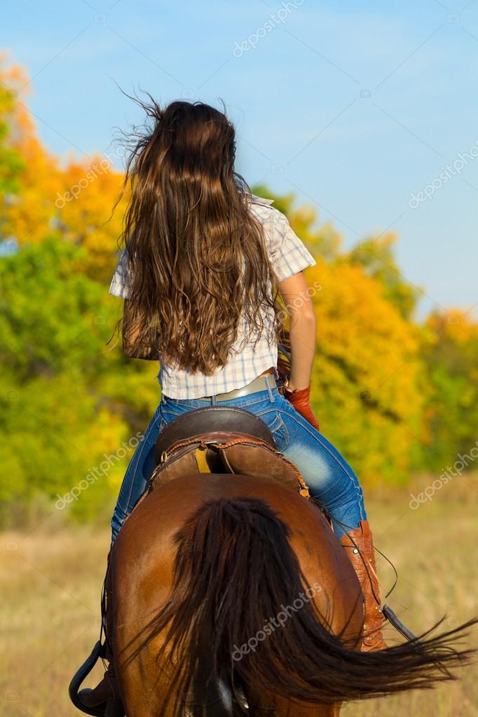 Woman in blue jeans riding  horse